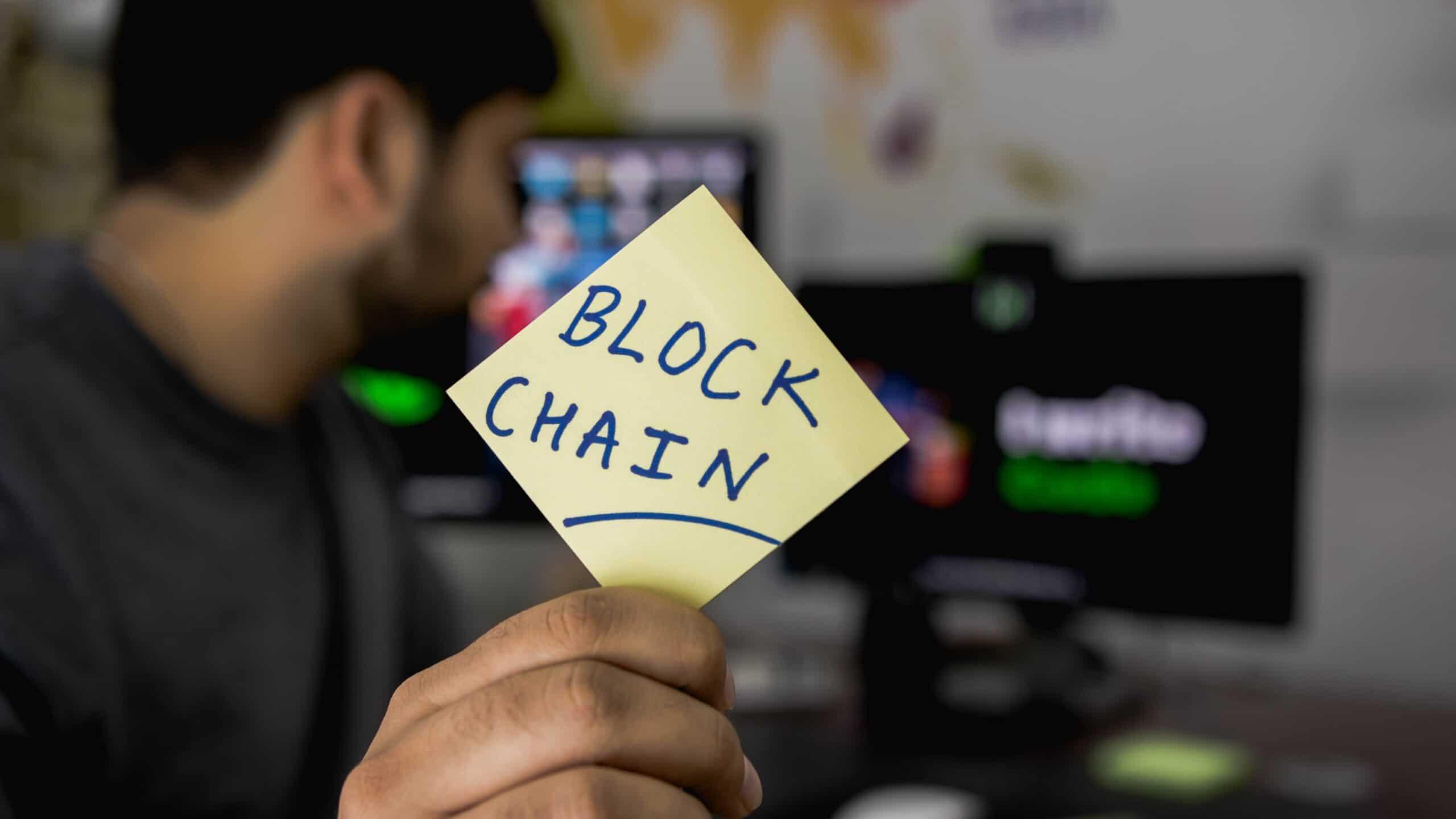 """ragazzo con post-it con su scritto """"blockchain"""""""